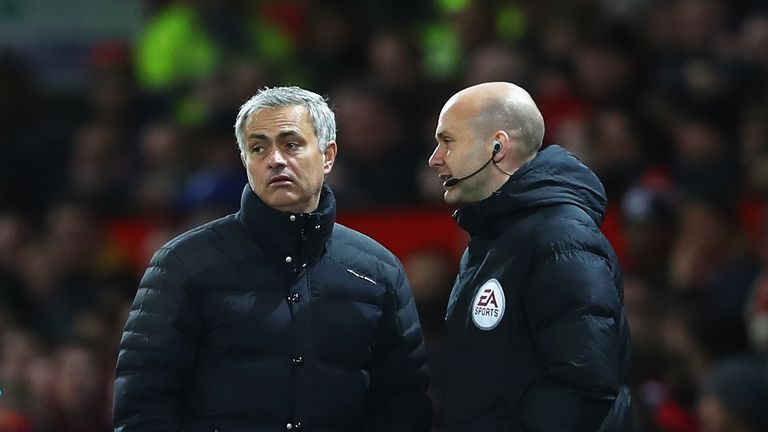 MANCHESTER, ENGLAND - NOVEMBER 27:  Jose Mourinho, Manager of Manchester United (L) speaks to Anthony Taylor, the fourth offical during the Premier League