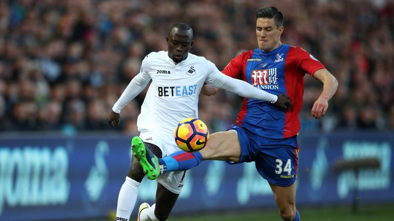 Swansea City's Modou Barrow and Crystal Palace's Martin Kelly (right) battle for the ball during the Premier League match at the Liberty Stadium, Swansea.