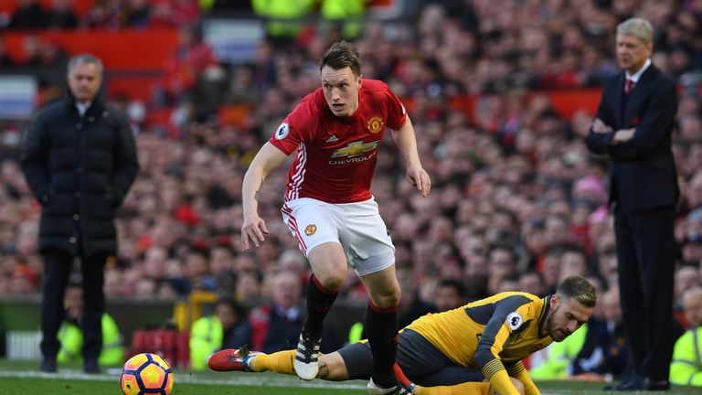 Manchester United defender Phil Jones (L) vies with Arsenal's Aaron Ramsey