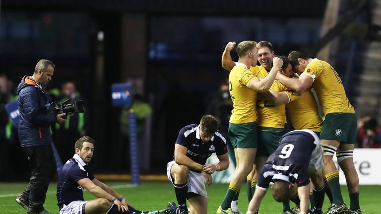 Greig Laidlaw (left) looks on as Australian players celebrate at the final whistle