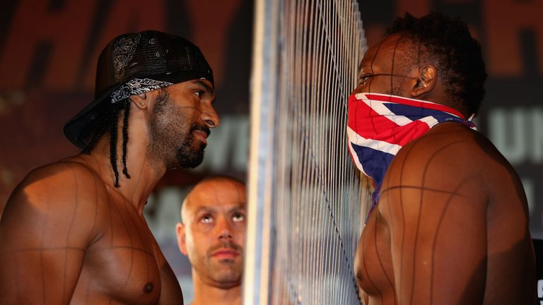 LONDON, ENGLAND - JULY 12:  David Haye (left) and Dereck Chisora eyeball each other as Haye's trainer Adam Booth (centre) looks on during the Weigh-In at T