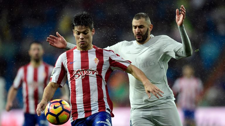 Sporting Gijon's defender Jorge Mere (L) vies with Real Madrid's French forward Karim Benzema during the Spanish league football match Real Madrid CF vs Re