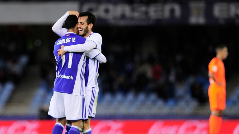 Real Sociedad's midfielder Juanmi (R) is congratulated by teammate Mexican forward Carlos Vela (L) after scoring his team's third goal during the Spanish l