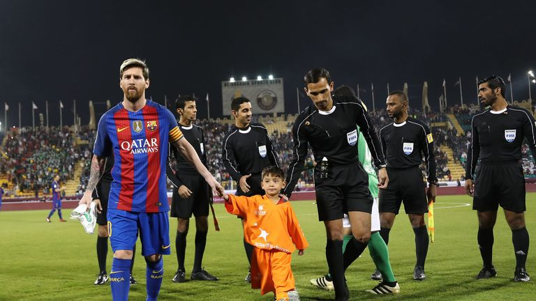 Lionel Messi holds the hands of Afghan boy Murtaza Ahmadi on the pitch before a friendly