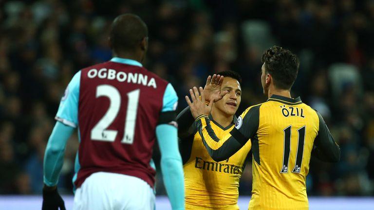 Mesut Oezil celebrates with Alexis Sanchez