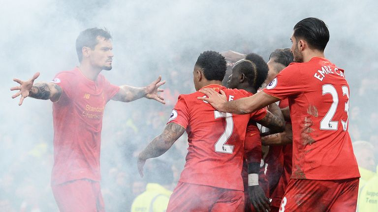 Sadio Mane and his Liverpool team-mates celebrate his late winner surrounded by smoke from a flare