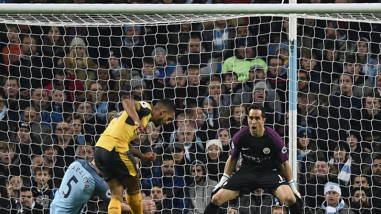 Arsenal's English midfielder Theo Walcott (C) scores his team's first goal past Manchester City's Chilean goalkeeper Claudio Bravo