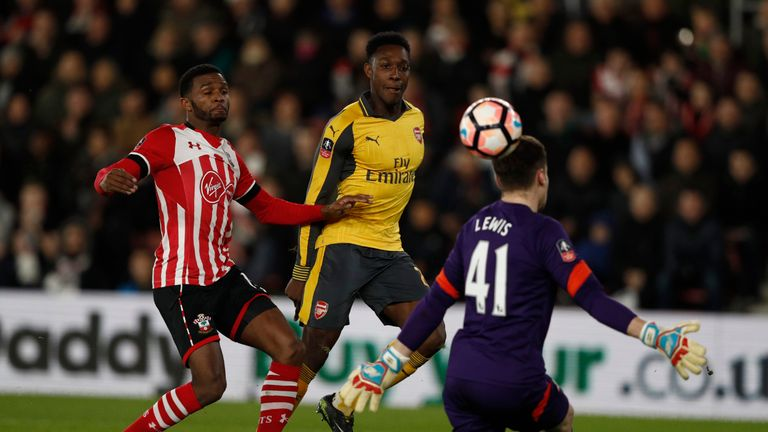 Arsenal's Danny Welbeck (C) chips the ball over Harry Lewis (R) to score his team's first goal