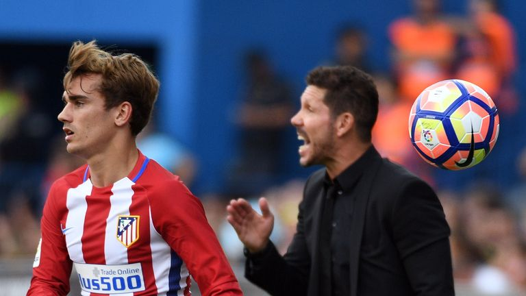 Atletico Madrid's French forward Antoine Griezmann (L) throws the ball beside Atletico Madrid's Argentinian coach Diego Simeone