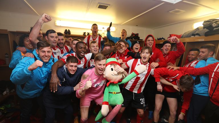 Lincoln City players celebrate in the dressing room after knocking Ipswich out of the FA Cup