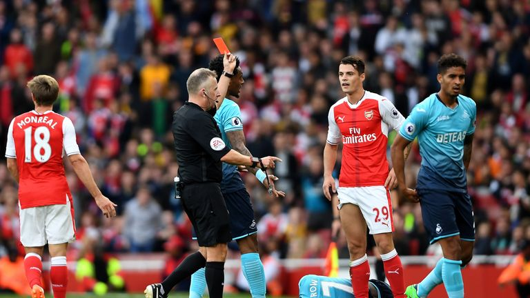 LONDON, ENGLAND - OCTOBER 15:  Referee Jonanthan Moss (L) shows Granit Xhaka of Arsenal (R) a red card during the Premier League match between Arsenal and