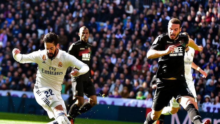 Real Madrid's midfielder Isco (L) kicks the ball to score during the Spanish league football match Real Madrid CF vs Granada FC at the Santiago Bernabeu st