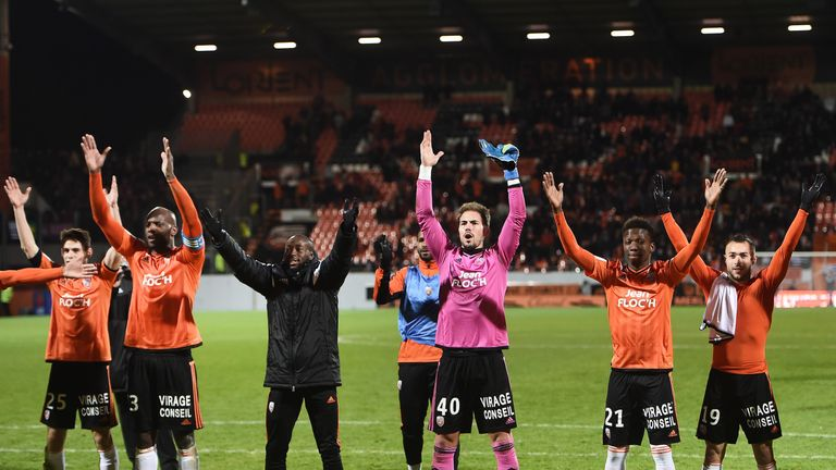 Lorient's players celebrate with their supporters after their victory against Guingamp