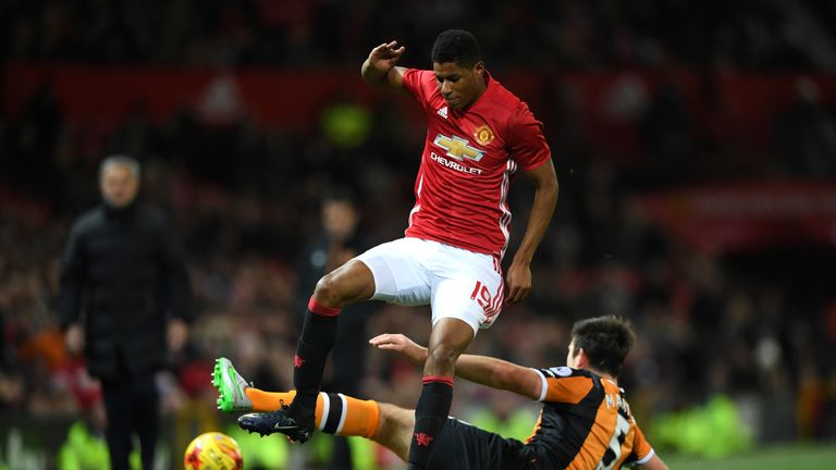 Marcus Rashford of Manchester United rides a tackle from Harry Maguire of Hull City