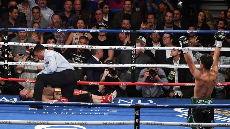 Referee Tony Weeks checks on Dejan Zlaticanin after he was knocked out by Mikey Garcia (R) in the third round