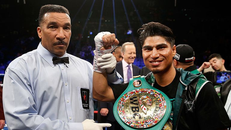 Mikey Garcia (R) poses with referee Tony Weeks after knocking out Dejan Zlaticanin in the third round to win the WBC lightweight