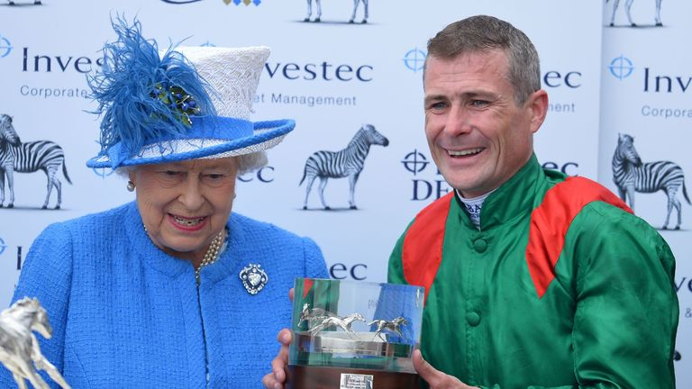 Britain's Queen Elizabeth II (L) presents jockey Pat Smullen with a trophy after winning the Derby on Harzand on the second day of the Epsom Derby Festival