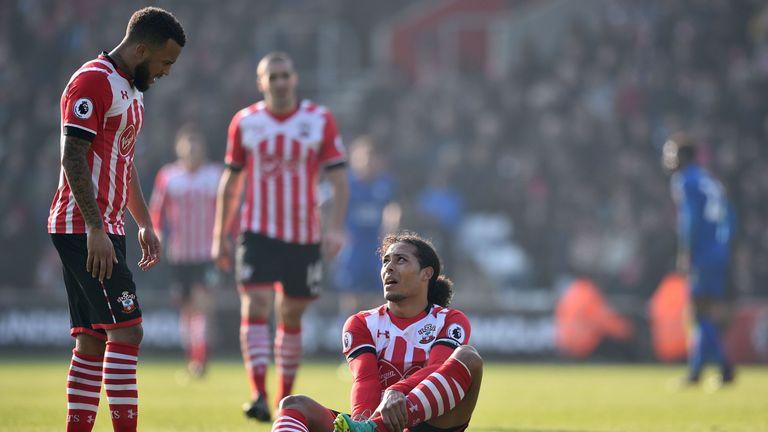 Southampton's Dutch defender Virgil van Dijk (C) sits down injured as Southampton's English defender Ryan Bertrand (L) looks on during the English Premier