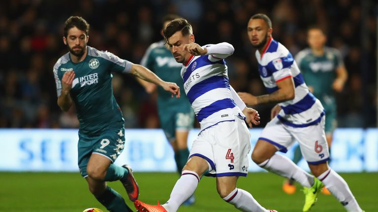 Grant Hall of QPR beats Will Grigg of Wigan Athletic to the ball