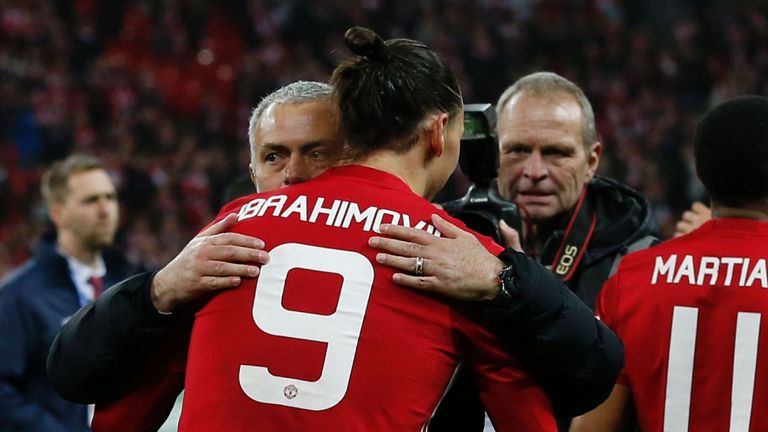 Manchester United's Swedish striker Zlatan Ibrahimovic embraces Manchester United's Portuguese manager Jose Mourinho as players celebrate on the pitch afte