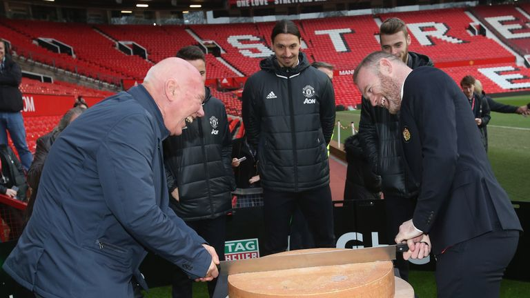 Wayne Rooney and Jean-Claude Biver cut a ceremonial cheese at the launch of a TAG Heuer Special Edition Manchester United Co-Branded Watch at Old Trafford