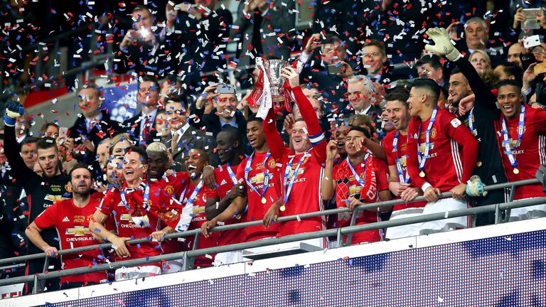 Wayne Rooney lifts the EFL Cup at Wembley Stadium