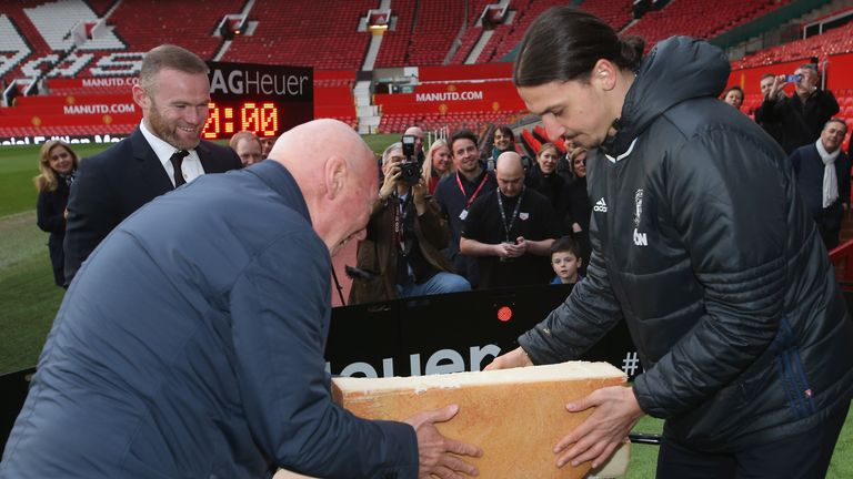 Zlatan Ibrahimovic and Jean-Claude Biver cut a ceremonial cheese at the launch of a TAG Heuer Special Edition Manchester United Co-Branded Watch