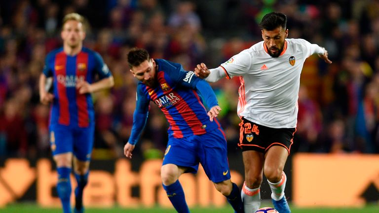 Lionel Messi (L) vies with Ezequiel Garay (R) during the Spanish league football match between Barcelona and Valencia