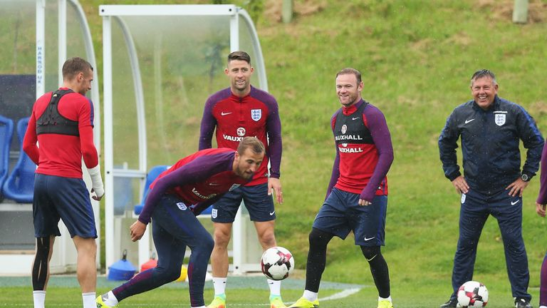 BURTON UPON TRENT, ENGLAND - SEPTEMBER 03: Gary Cahill and Wayne Rooney of England laugh with Craig Shakespeare (R) during a training session at St. George