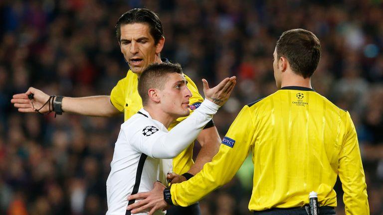 Paris Saint-Germain's Italian midfielder Marco Verratti (C) speaks to German referee Deniz Aytekin (back) and assistant referee during the UEFA Champions L