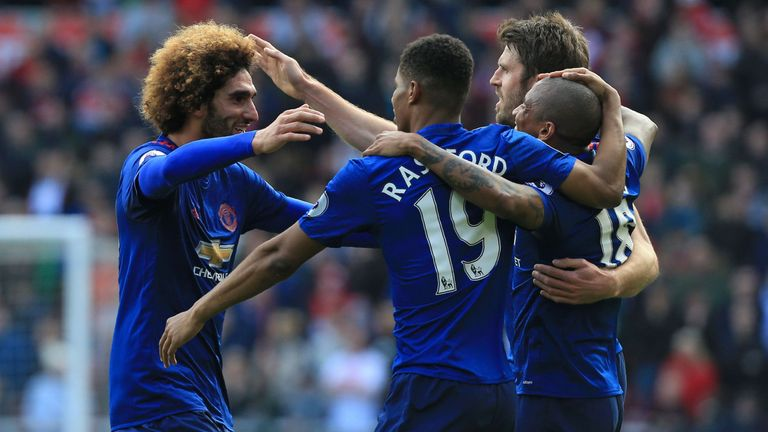 Manchester United's Belgian midfielder Marouane Fellaini (L) celebrates with teammates after scoring the opening goal of the English Premier League footbal