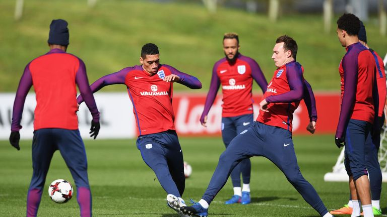 BURTON-UPON-TRENT, ENGLAND - MARCH 21: Chris Smalling of England tackles Phil Jones of England in training