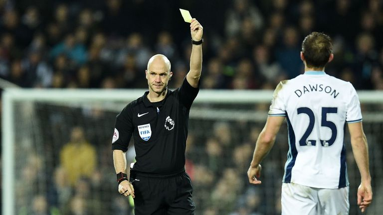 Referee Anthony Taylor shows a yellow card to West Bromwich Albion's English defender Craig Dawson (R) for a challenge on Manchester United's Swedish strik