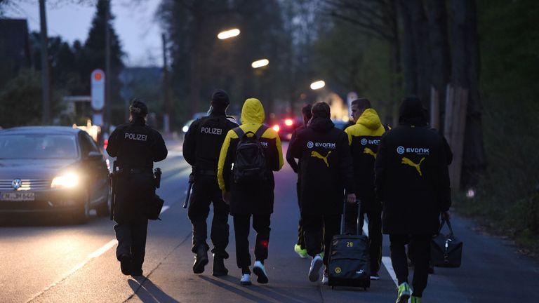Police escort Dortmund's players after their team bus was damaged by three explosions