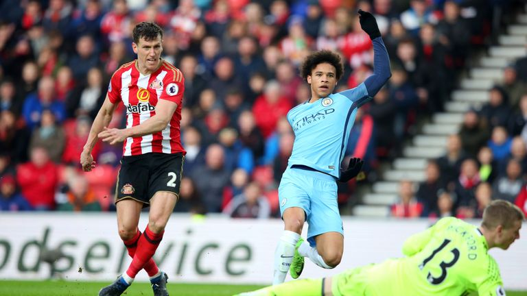 Leroy Sane of Manchester City (R) scores his sides second goal while Billy Jones of Sunderland (L) attempts to stop him