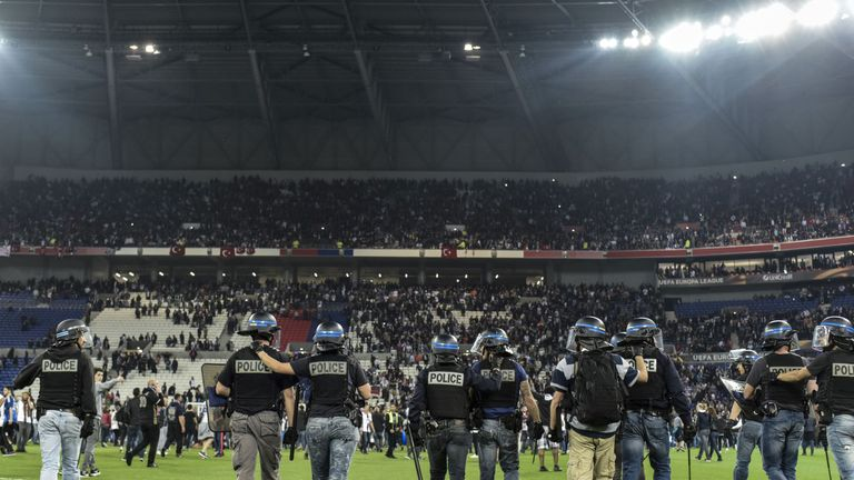 Police stand on the pitch after Besiktas' and Lyon's supporters fought before the Europa League quarter-final