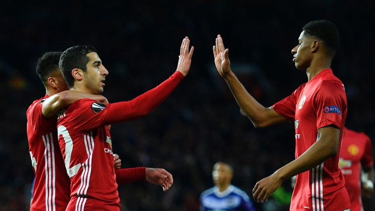 Manchester United's Armenian midfielder Henrikh Mkhitaryan (L) high-fives with Manchester United's English striker Marcus Rashford (R) after scoring the op