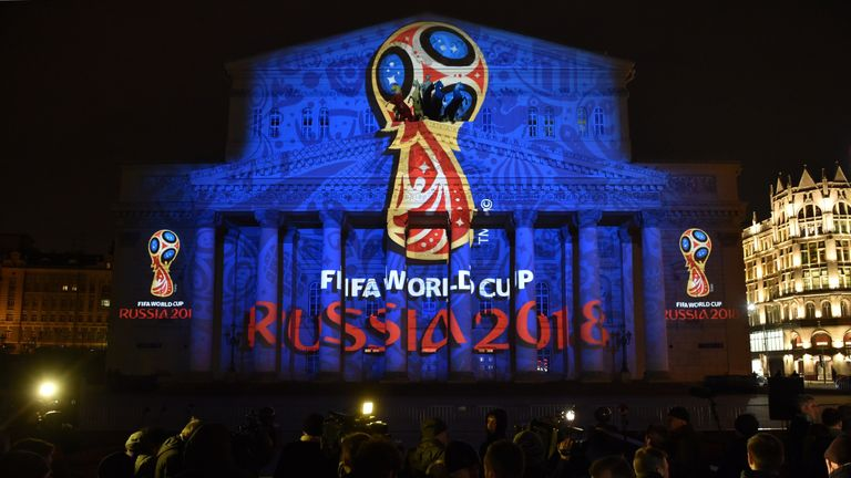 People watch as the facade of Moscow's historic Bolshoi Theatre is illuminated with the official emblem of the 2018 FIFA World Cup to be held in Russia