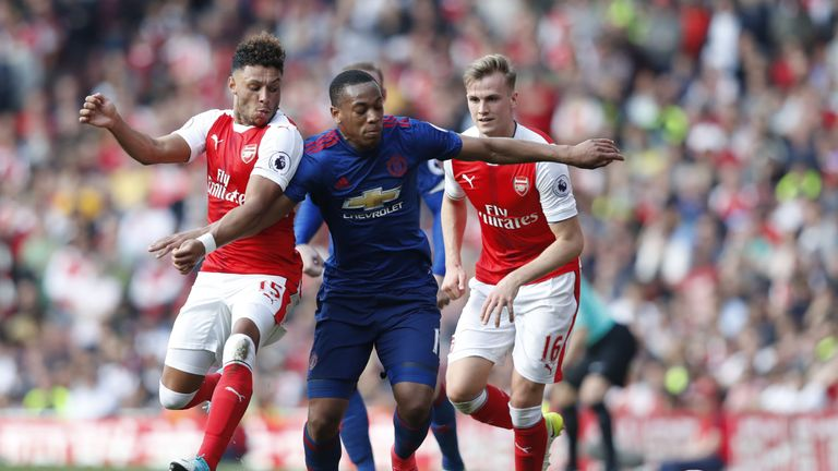 Arsenal's English midfielder Alex Oxlade-Chamberlain (L) and Arsenal's English defender Rob Holding (R) block Manchester United's French striker Anthony Ma