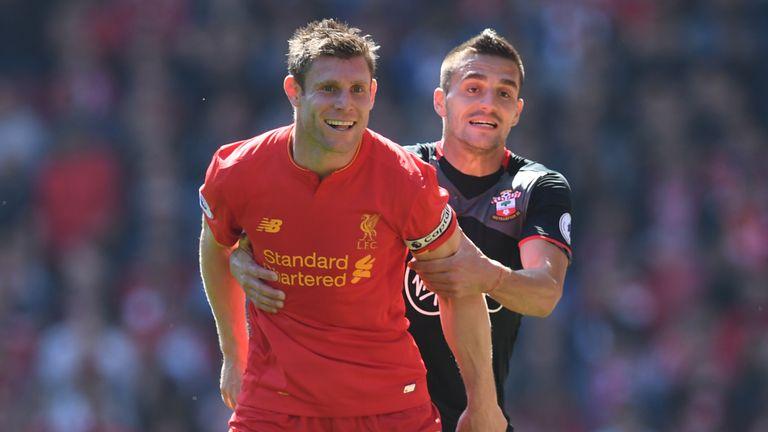 Liverpool's English midfielder James Milner (L) is held by Southampton's Serbian midfielder Dusan Tadic