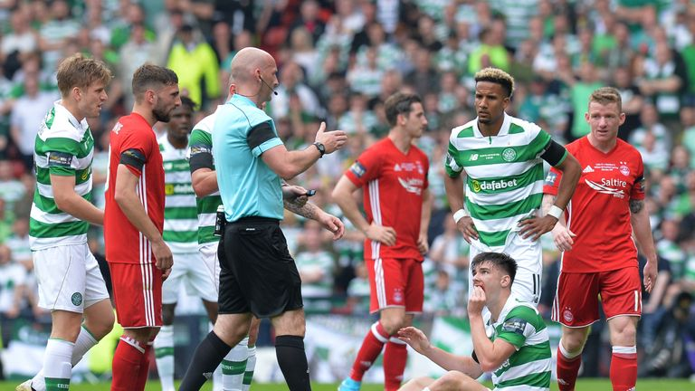 Kieran Tierney sits on the turf with a facial injury that forced him to be substituted in the first half