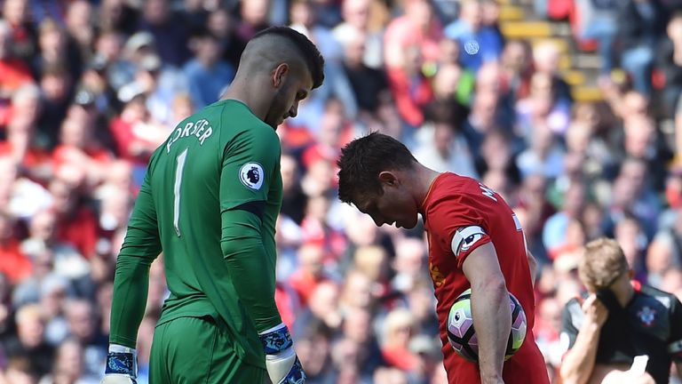 Southampton's English goalkeeper Fraser Forster (L) eyes up Liverpool's English midfielder James Milner before he takes a penalty during the English Premie