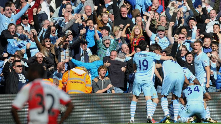 Manchester City's Argentinian striker Sergio Aguero celebrates his late winning goal with team-mates during the English Premier League football match betwe