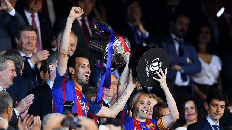 MADRID, SPAIN - MAY 27:  Sergio Busquets (L) and Andres Iniesta of FC Barcelona hold up the trophy after winning the Copa Del Rey Final between FC Barcelon