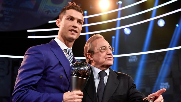 Real Madrid and Portugal's forward and winner of The Best FIFA Mens Player of 2016 Award Cristiano Ronaldo (L) poses on stage with his trophy next to Real