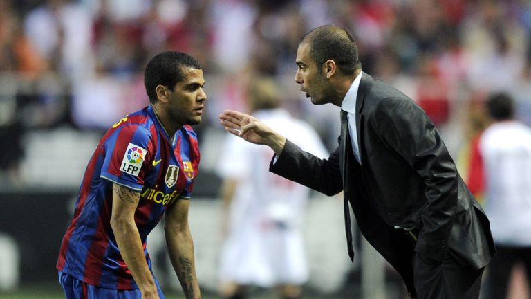 Barcelona's coach Pep Guardiola (R) speaks with Barcelona's Brazilian defender Dani Alves (L) during their Spanish league football match beetwen Sevilla an