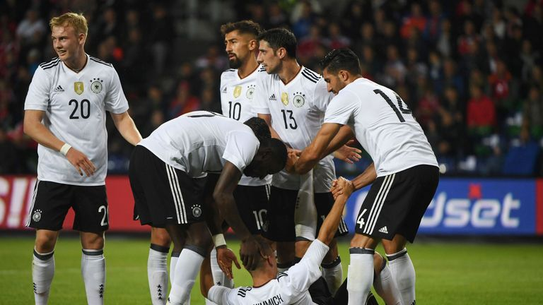 Germany's defender Joshua Kimmich is helped by his temmates for cram after scoring during the friendly football match between Denmark and Germany