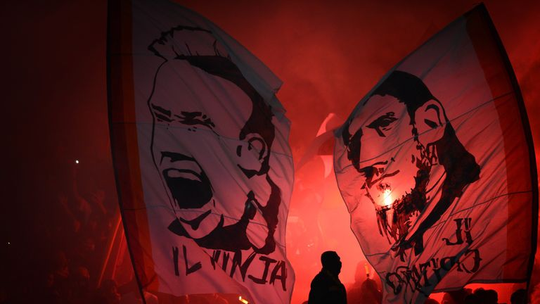 Indonesian fans light up flares and wave banners depicting the portraits of AS Roma's Italian team captain Francesco Totti and Radja Nainggolan
