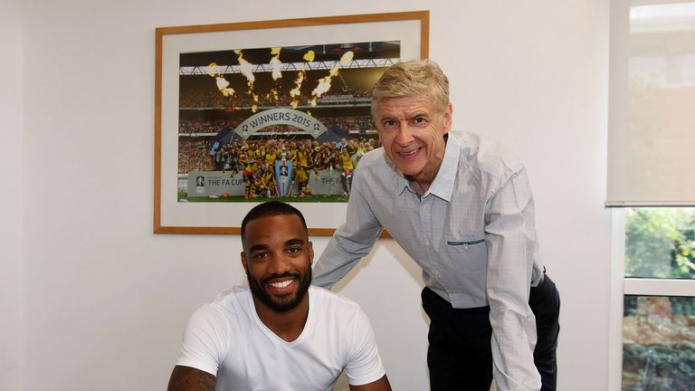 Alexandre Lacazette signs his contract with Arsenal manager Arsene Wenger at London Colney
