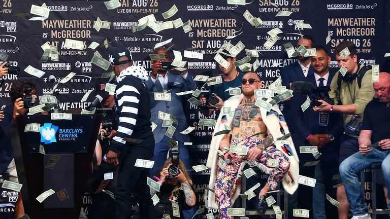Floyd Mayweather Jr. looks on as money rains down on Conor McGregor during the Floyd Mayweather Jr. v Conor McGregor World Press Tour